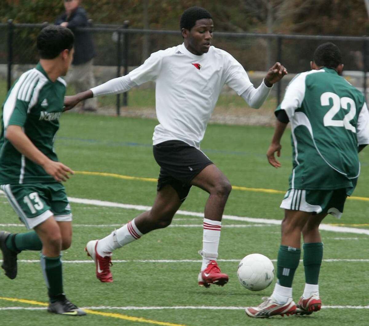 Greenwich High School's lone scorer Kenny Doublette threads his way through Norwalk's Danny Quintero and Mike Broncati during Tuesday afternoons Class LL first round game at Greenwich High School.