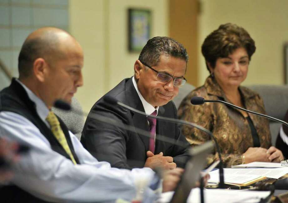 Dr. Robert  Durón resigns his position as superintendent of the SAISD during a Monday evening board meeting. Board president Ed Garza (left) and board member Olga Hernandez (right) listen. Photo: Robin Jerstad/For The Express-News