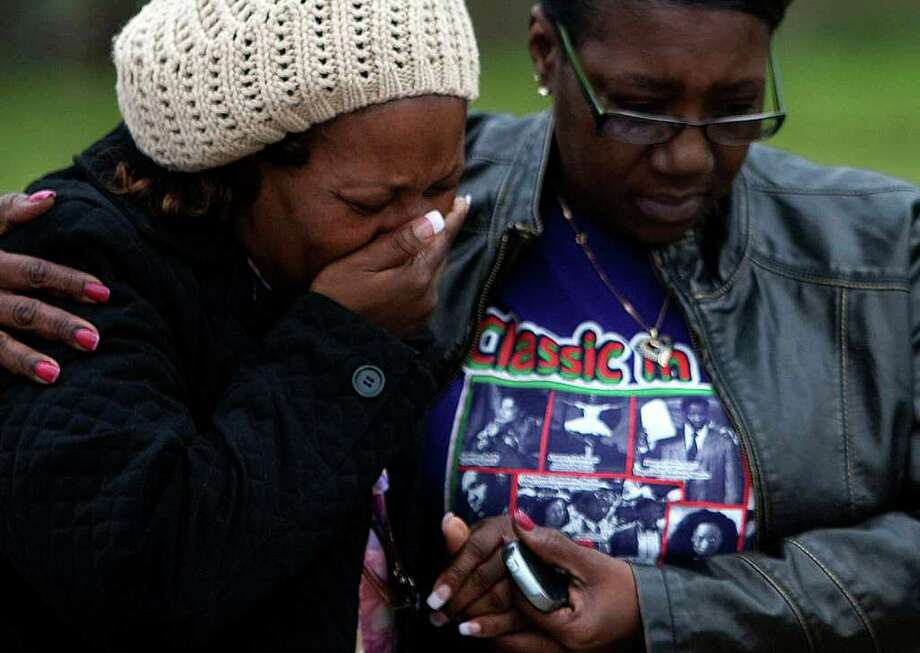 Charlotte Bill, left, is consoled by cousin Geraldine Webb Qualls after learning the bodies of her daughter and son-in-law were found at a charred complex in north Harris County five days after the fire. Photo: Johnny Hanson / © 2012  Houston Chronicle