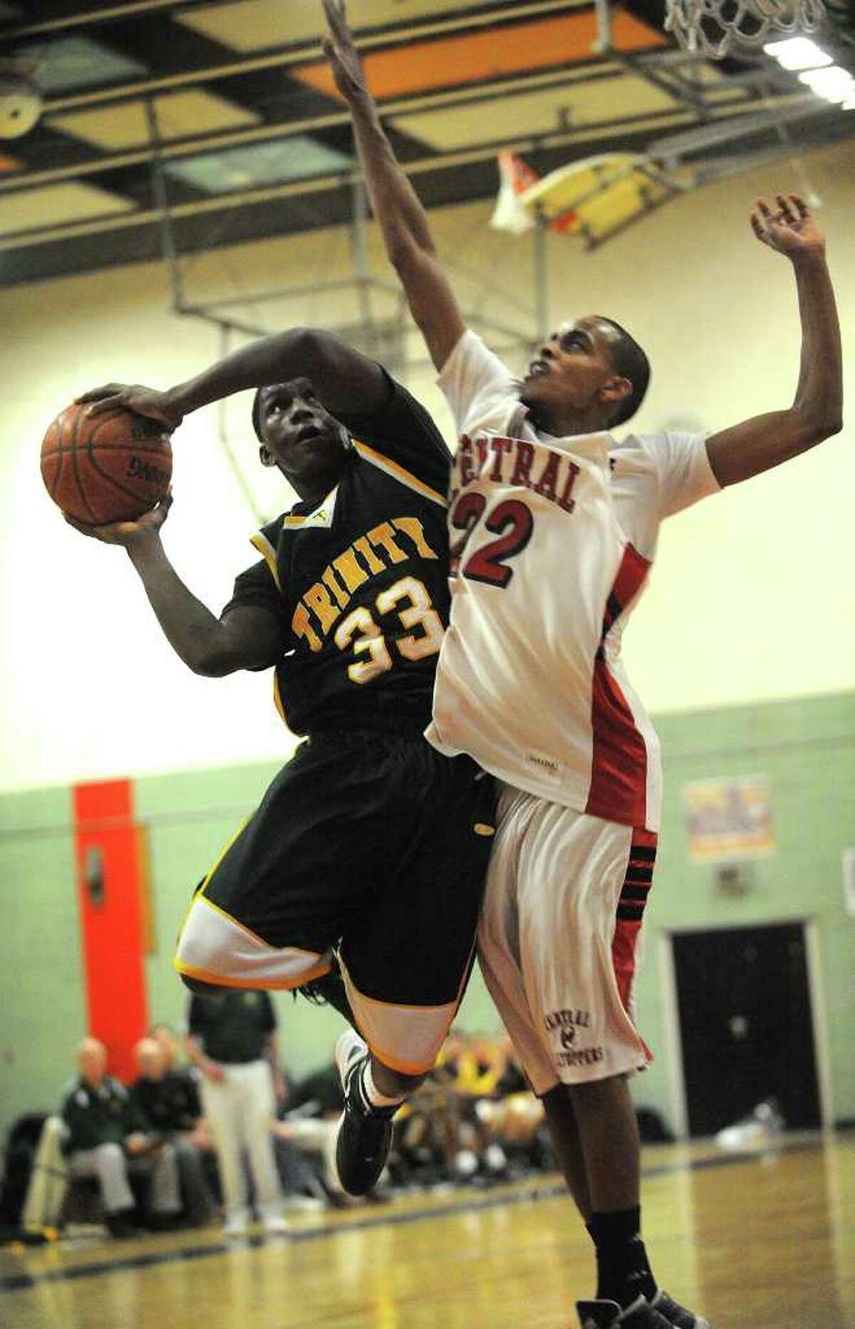 Trinity Catholic's Kevin Leumene, left, drives to the basket defended by Central's Yassar Abdul at Central High School in Bridgeport on Monday, February 20, 2012.