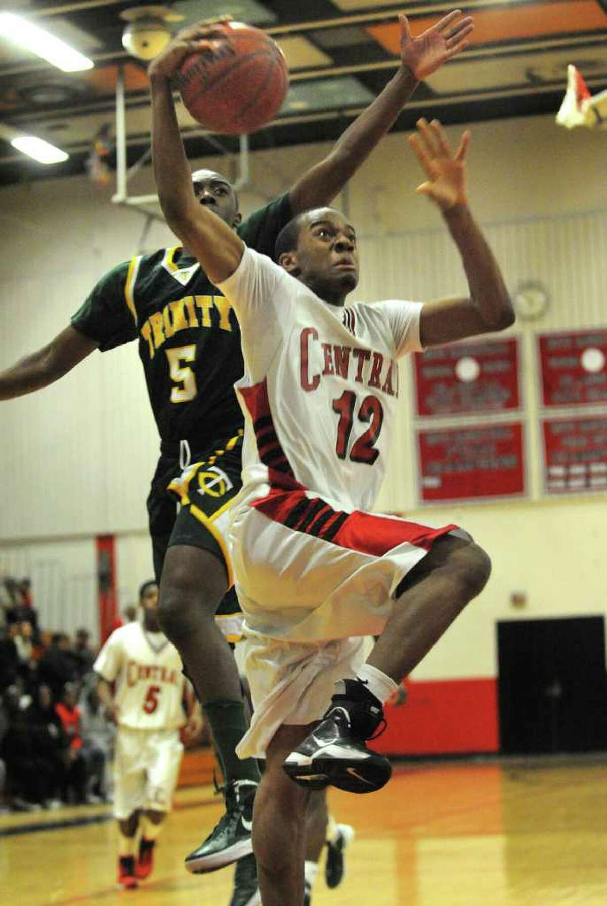 Trinity Catholic's Brandon Wheeler, left, looks for the block as Central's Josh Wilkerson drives to the basket during their FCIAC matchup at Central High School in Bridgeport on Monday, February 20, 2012.