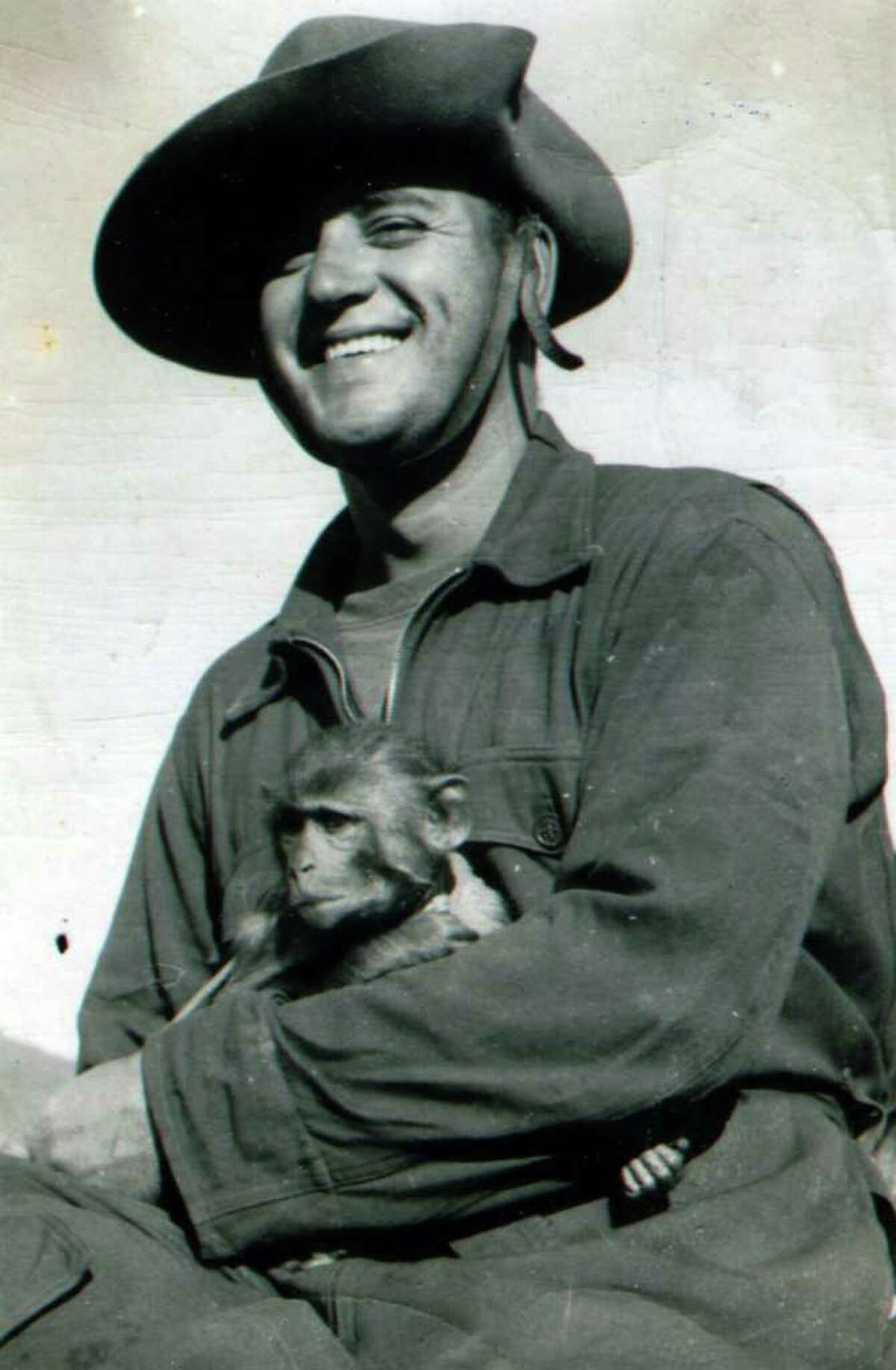 """Ed With is pictured with a pet monkey he called the """"Commander,"""" at the base camp in Burma, circa 1944. (Courtesy Ed With)"""