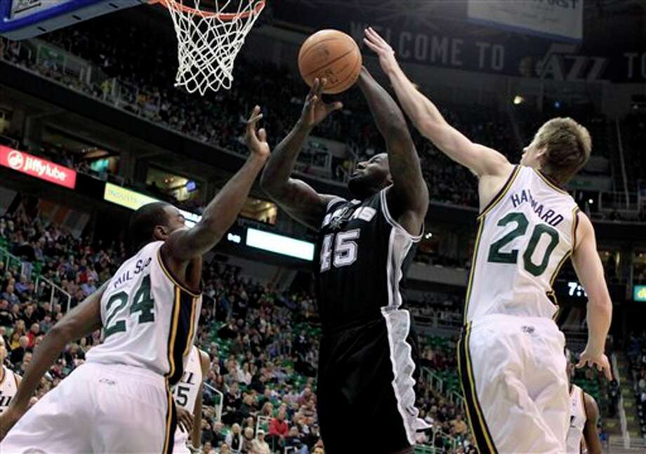 Spurs forward DeJuan Blair (45) takes a shot while defended by Jazz forward Paul Millsap (24) and guard Gordon Hayward (20) during the first half on an NBA basketball game, Monday, Feb. 20, 2012, in Salt Lake City. (AP Photo/Jim Urquhart) (AP)