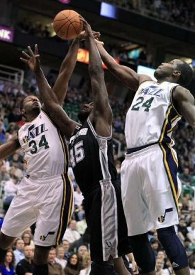 Spurs forward DeJuan Blair (45) goes for a rebound while defended by Jazz forwards C.J. Miles (34) and Paul Millsap (24) during the first half on an NBA basketball game, Monday, Feb. 20, 2012, in Salt Lake City. (AP Photo/Jim Urquhart) (AP)
