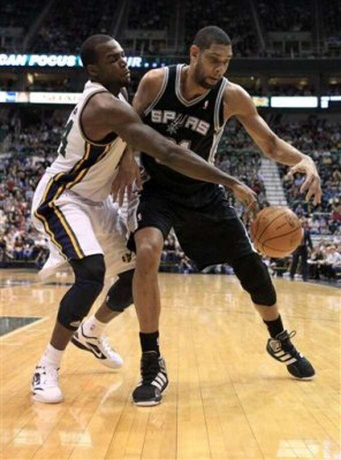 Spurs center Tim Duncan, right, is defended by Jazz forward Paul Millsap during the first half on a NBA basketball game, Monday, Feb. 20, 2012, in Salt Lake City. (AP Photo/Jim Urquhart) (AP)