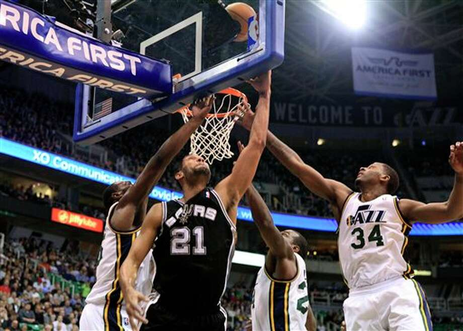 Spurs center Tim Duncan (21) attempts a shot while defended by Jazz center Al Jefferson, left, forwards Paul Millsap, second from right and C.J. Miles (34) during the first half on a NBA basketball game, Monday, Feb. 20, 2012, in Salt Lake City. (AP Photo/Jim Urquhart) (AP)
