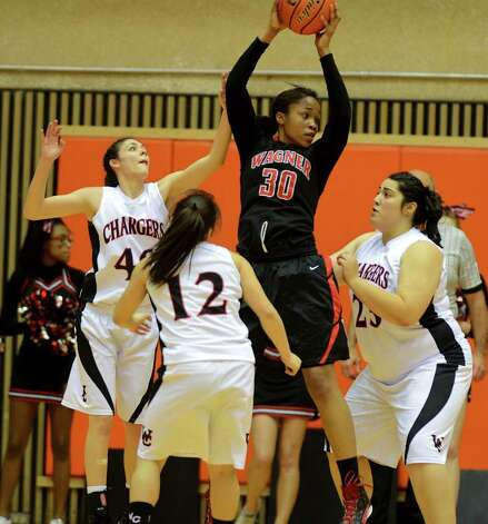 Wagner's Tesha Smith comes down with the ball between three Churchill defenders during a UIL 5A girls third round playoff  basketball game between the Wagner T-Birds and the  Churchill Chargers at the UTSA Convocation Center In San Antonio, Texas on February 20, 2012.