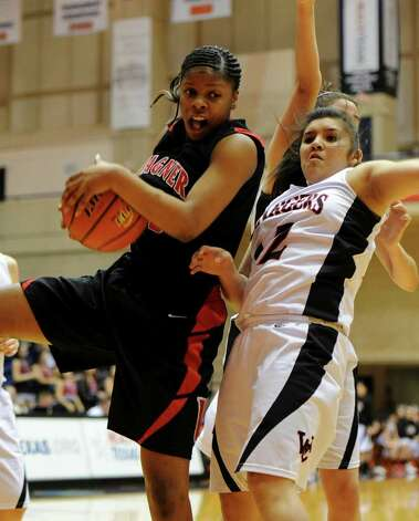 Wagner's Kaelynn Wilson (33) grabs a rebound in front of Churchill's Mikki Flores (12) during a UIL 5A girls third round playoff  basketball game between the Wagner T-Birds and the  Churchill Chargers at the UTSA Convocation Center In San Antonio, Texas on February 20, 2012.