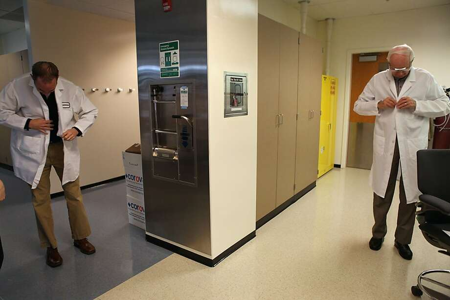 Paul Muchowski (left) and his dad, Joseph Muchowski, adjust their lab coats at the Gladstone Institutes in San Francisco, an affiliate of UCSF. Photo: Liz Hafalia, The Chronicle
