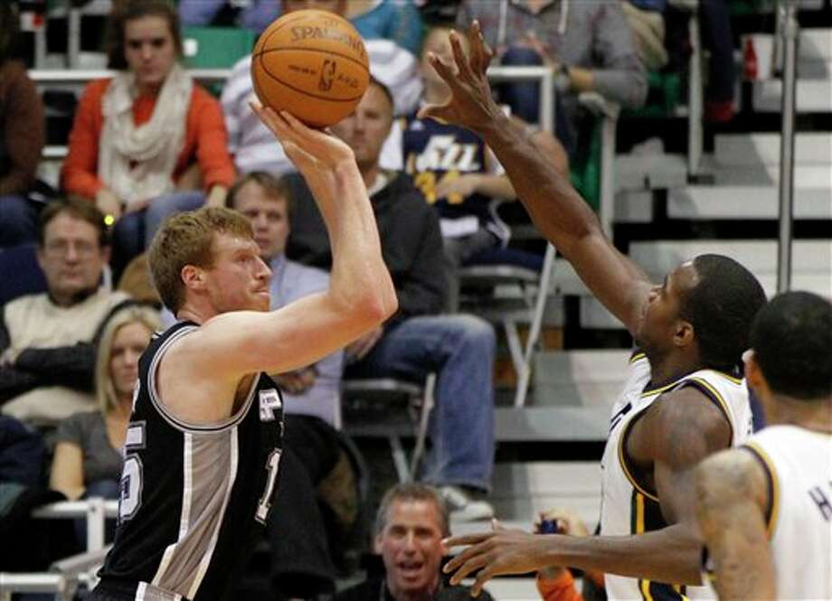 San Antonio Spurs forward Matt Bonner, left, shoots over Utah Jazz's Paul Millsap during the second half on a NBA basketball game, Monday, Feb. 20, 2012, in Salt Lake City. The Spurs won 106-102. (AP Photo/Jim Urquhart) (AP)