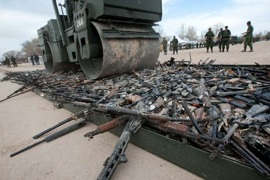 A military asphalt roller spins over a stack of weapons to destroy them in Ciudad Juarez, Mexico (AP Photo/Eduardo Verdugo)
