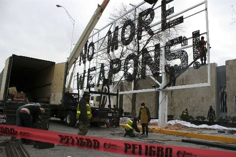 "Soldiers put final touches on a giant ""No More Weapons"" billboard made with crushed firearms placed near the U.S. border in Ciudad Juarez, Mexico. (AP Photo/Raymundo Ruiz) ---"