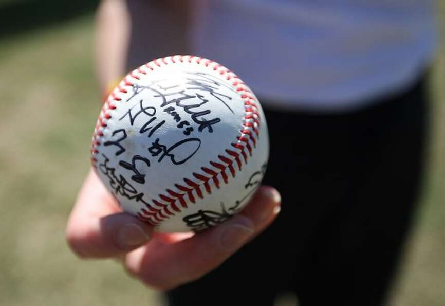Lee Nichols shows off her autographed baseball from the first day of workouts. (Karen Warren / Houst