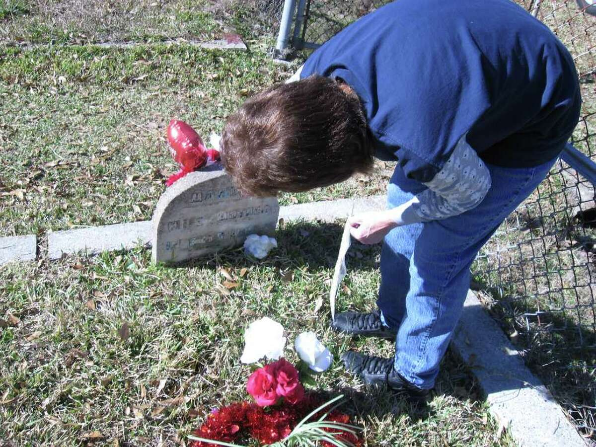 """Brenda Slaughter replaces a sign she has made for her daughter's headstone. While the stone designates a resting place for """"MANDY,"""" Slaughter's sign has the name """"Amanda Gail Slaughter."""""""