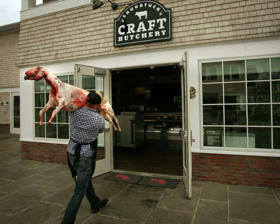 Ryan Fibiger, co-owner of Saugatuck Craft Butchery at 575 B Riverside Avenue in Westport, carries a lamb into his shop. Photo: Brian A. Pounds / Connecticut Post