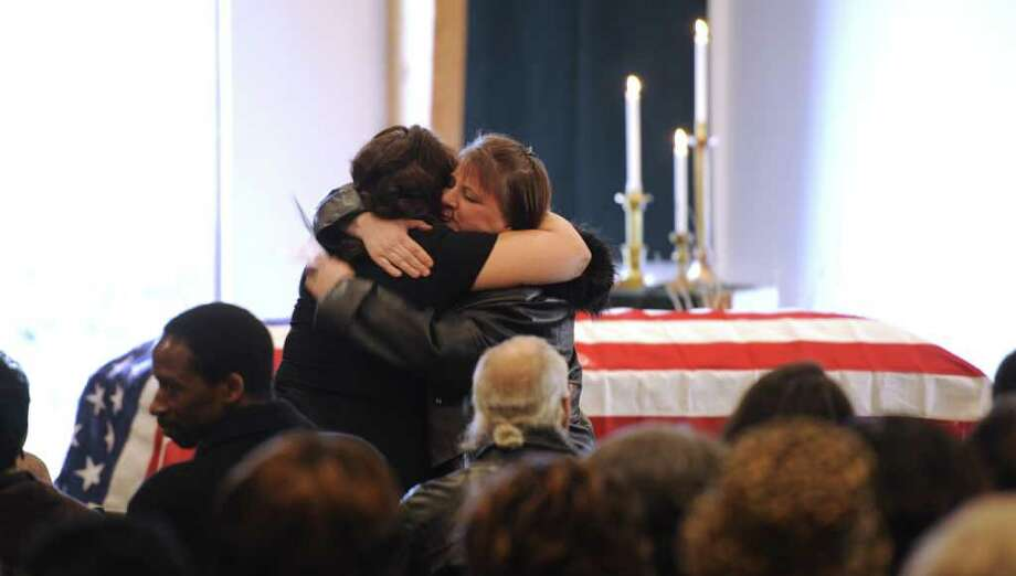 Relatives of Clarence Dart hug before the funeral ceremony at the United Methodist Church in Saratoga Springs, N.Y. on Tuesday, Feb. 21, 2012.  Dart, who flew 95 combat missions in World War II and was shot down twice, was a member of the legendary Tuskegee Airmen, the elite African-American pilots, was buried with full military honors at the Green Ridge Cemetery in Saratoga Springs.       ( Skip Dickstein / Times Union) Photo: Skip Dickstein / 2011