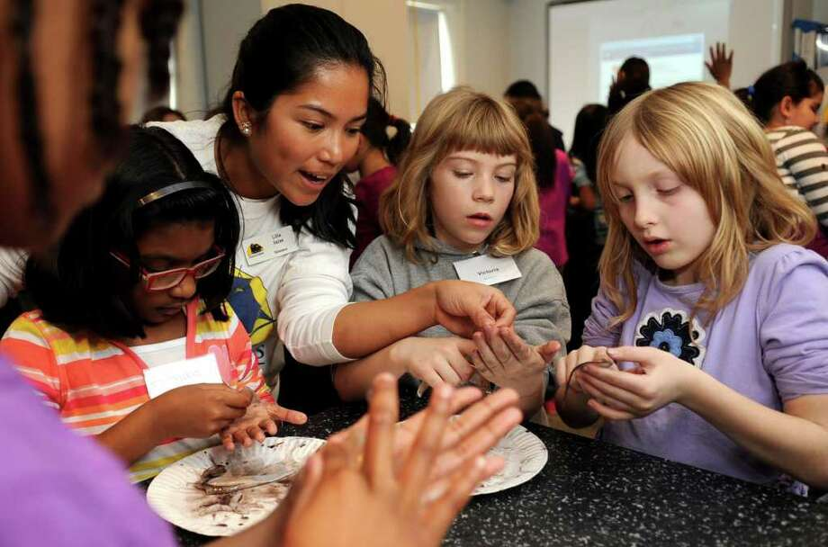 Instructor Lilia Salas helps, from left, Rithika Harikrishna, 9, Victoria Bradford, 9, and Abigail Morse, 8, dissect a squid during the Science Stars program at SoundWaters Coastal Center in Stamford on Tuesday, February 21, 2012. Photo: Lindsay Niegelberg / Stamford Advocate