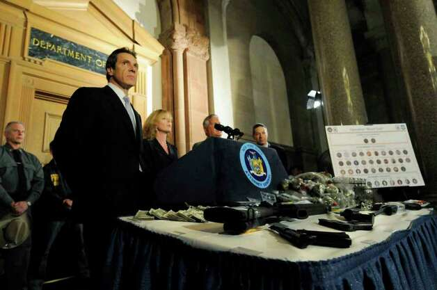 "In this photo from September 2010, then-state Attorney General Andrew Cuomo shows cash, drugs and guns recovered as part of an investigation called ""Operation Blood Trail.""  State prosecutors have secured their 40th conviction in the case. (Michael P. Farrell / Times Union archive) Photo: Michael P. Farrell"