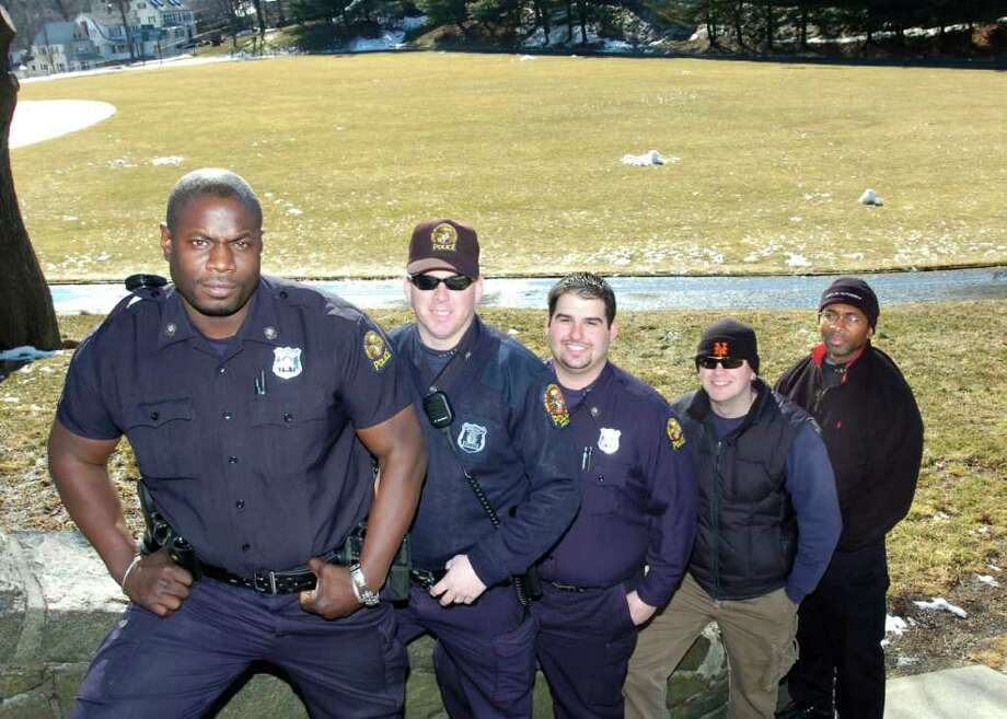 Greenwich police officer Donnell Fludd, left, was charged Monday with second-degree stalking, second-degree harassment and disorderly conduct after the department received a complaint from a woman Fludd was formerly dating. Fludd, one of the co-founders of the department's youth flag football league, is pictured in 2007 with other officers involved in organizing the league. PHOTO/BOB LUCKEY Photo: GT / 00000087A