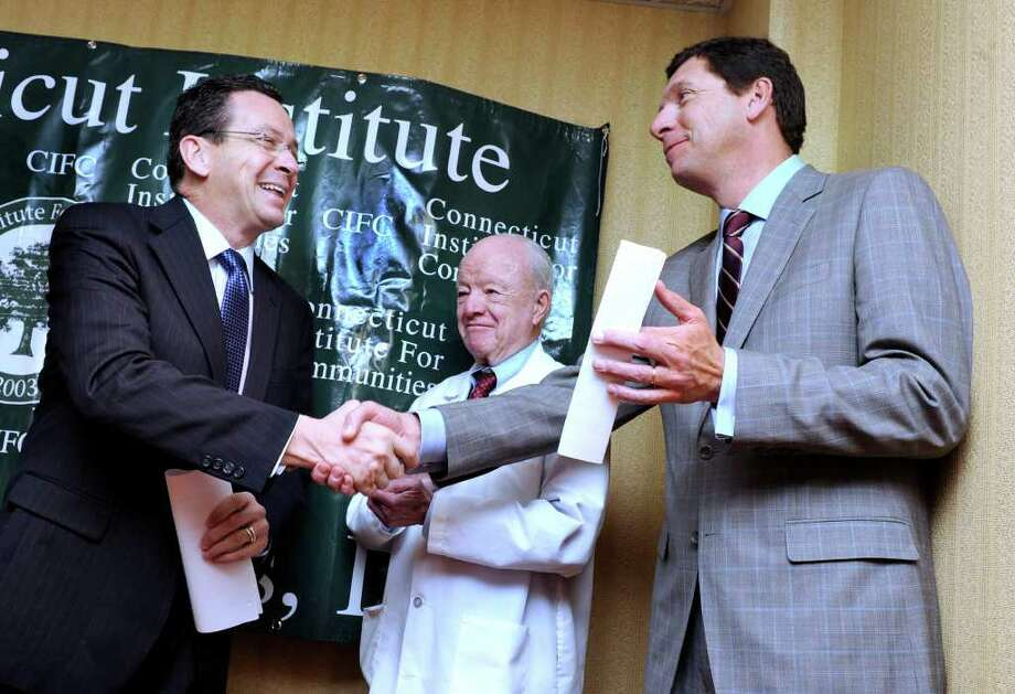 Gov. Dannel P. Malloy, left, shake hands with Dr. John Murphy, president and CEO of Western Connecticut Health Network. Dr. Thomas Draper, medical director at Connecticut Institute for Communities, Inc. is in the center. Local and state officials, including Malloy announced a new primary care physician residency program in the city. Photo taken Tuesday, Feb. 21, 2012. Photo: Carol Kaliff / The News-Times