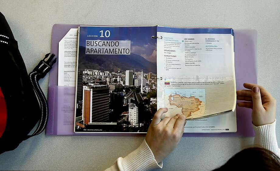 San Francisco State University sophomore, Ginamarie Gianandrea, with her $150 unbound spanish textbook,  on Thursday Feb. 16, 2010. New initiatives in California take aim at reducing the cost of textbooks. One company has just signed an agreement  with California State Universities to offer its books electronically for a 60 percent discount. Photo: Michael Macor, SFC