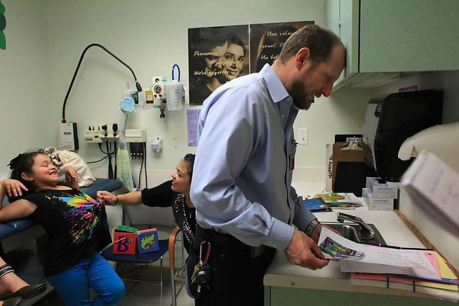 Dr. Robert Savio (right), chief of pediatrics at Highland looks through the medical files of Esmeralda Pena (left), 7,  and Yazmin Pena (not shown), 10, during a visit to Highland Hospital on Wednesday, February 8, 2012 in Oakland, Calif. Photo: Lea Suzuki, The Chronicle