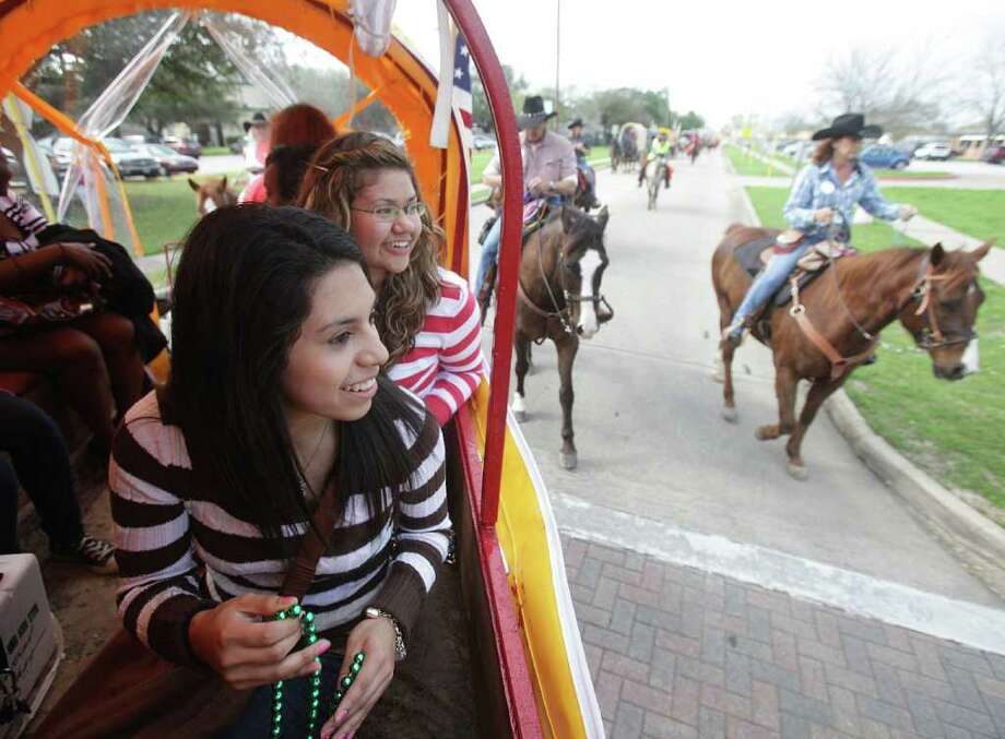 Chinquapin Academy students Jennifer Hernandez, 17, and Alejandra Badillo, 17, smile as they get ready to throw beads to spectators during the Texas Independence Trail Ride while learning what it's like to be a female Wagon Boss.  The girls are part of an organization called Girls Inc. of Greater Houston, an organization that seeks to inspire all girls to be strong, smart and bold. Photo: Mayra Beltran, Houston Chronicle / © 2012 Houston Chronicle