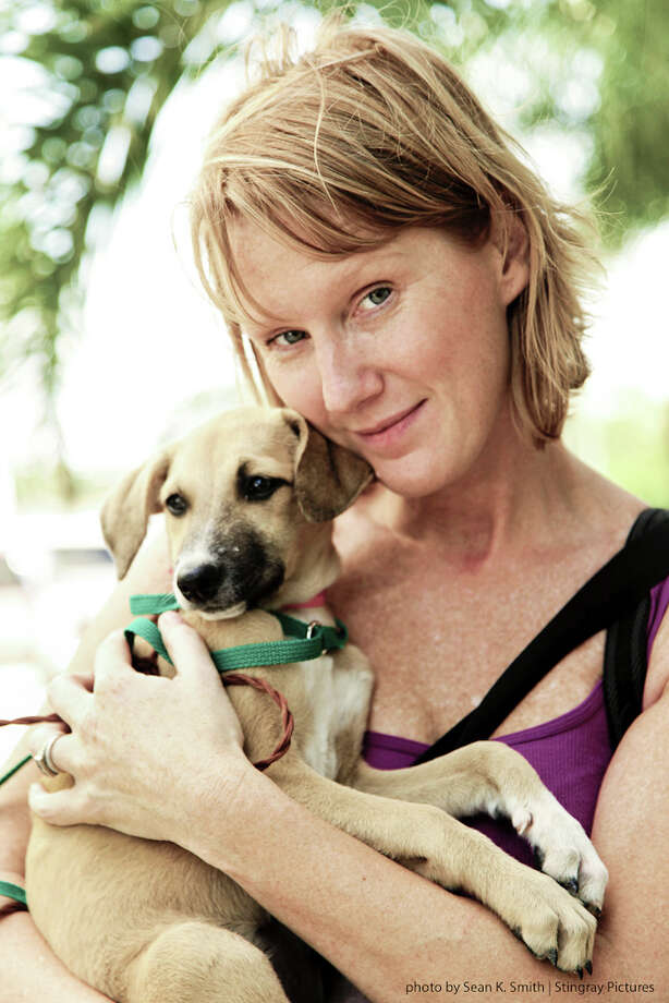 Saratoga Springs photographer Tracey Buyce holds a puppy at a free sterilization clinic put on by CANDi (Cats and Dogs International) in Cancun, Mexico. Buyce volunteered at the clinic for a week in January 2012.