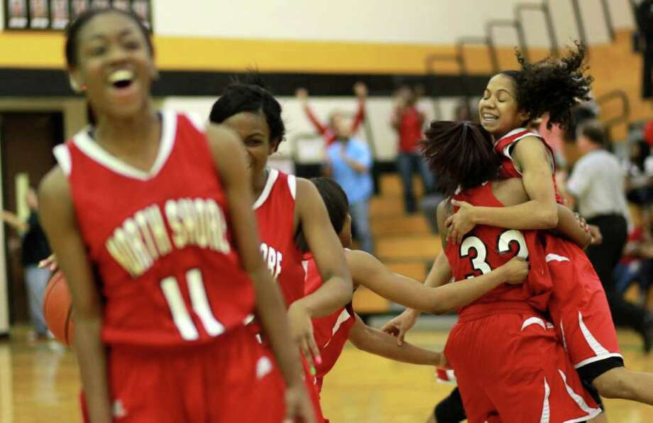 North Shore High School's Karina Williams, facing and her teammates celebrate after beating Hightower High School in a 5-A Regional Quarter Final basketball game, Tuesday, Feb. 21, 2012, Pasadena Memorial High School  in Pasadena. Photo: Nick De La Torre, Houston Chronicle / © 2012  Houston Chronicle
