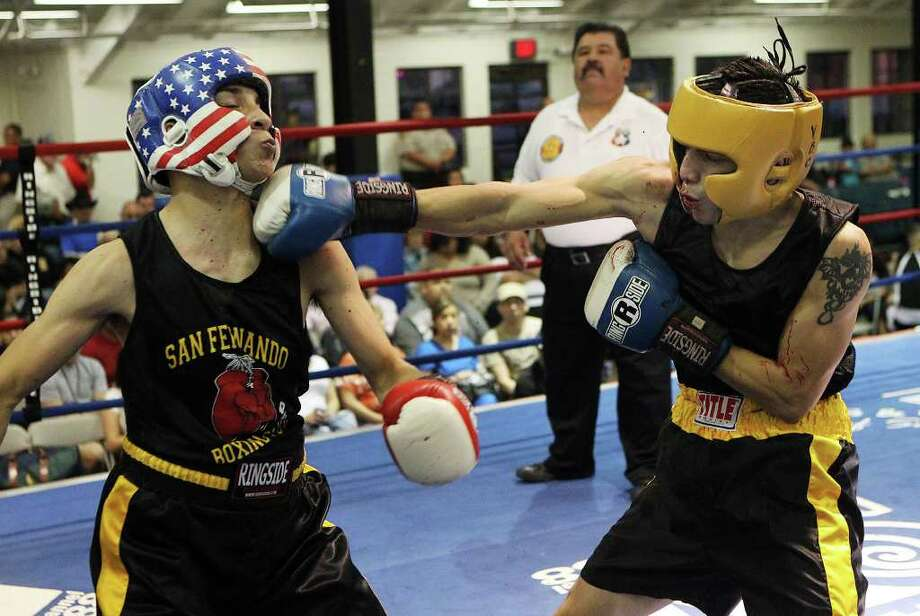 Juan Ontiveros (right) of Villar Boxing Club lands a punch to the chin of Jesse Rodriguez of San Antonio Parks & Rec. during their bout at the 2012 Regional Golden Gloves tournament at Woodlawn Gym on Tuesday, Feb. 21, 2012. Ontiveros received a bloodied nose in his first bout which he eventually won by decision. Kin Man Hui/San Antonio Express-News Photo: Kin Man Hui, ~ / San Antonio Express-News