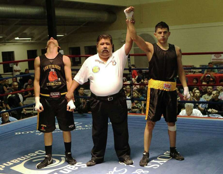 Juan Ontiveros (right) of Villar Boxing Club is declard the winner his opponent Jesse Rodriguez of San Antonio Parks & Rec. expresses his dismay after their bout at the 2012 Regional Golden Gloves tournament at Woodlawn Gym on Tuesday, Feb. 21, 2012. Kin Man Hui/San Antonio Express-News Photo: Kin Man Hui, ~ / San Antonio Express-News