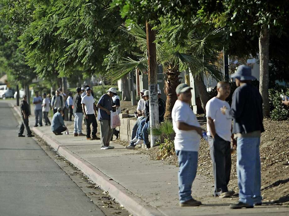Day laborers crowd the sidewalk outside a Home Depot store hoping to catch a day job Thursday Oct. 23, 2008 in San Diego. Most of the those seeking work are migrants and many say they are considering heading back to their country of origin because of the slumping U.S. economy.  (AP Photo/Lenny Ignelzi) Photo: Lenny Ignelzi, AP 2008