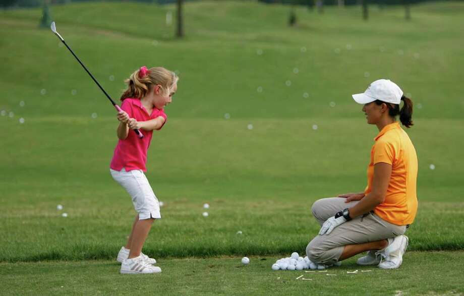 Aurora Kirchner-McClain, right, a teaching pro at Kingwood Country Club whose students are more than 60 percent juniors, recommends parents invest in a decent-priced set of clubs because cheaper clubs are harder to hit. Photo: KAREN WARREN / Houston Chronicle