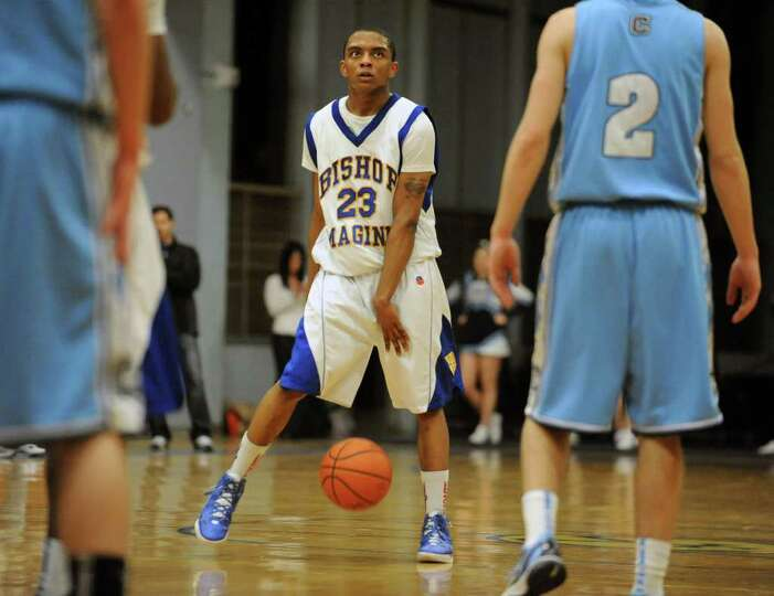 Bishop Maginn's Demere Hannah dribbles the ball between his legs as he looks at the clock during a b