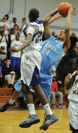 Columbia's Jahlil Nails drives to the basket  against Bishop Maginn's Derrek Thomas during a basketb