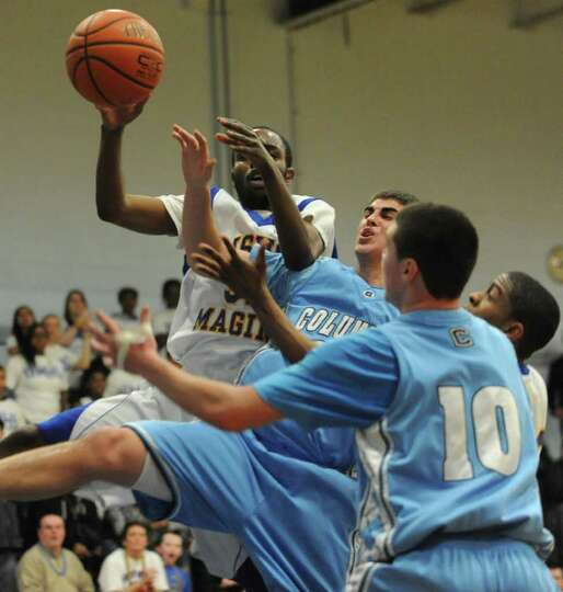 Bishop Maginn and Columbia players fight for a rebound during a basketball game Tuesday, Feb. 21, 20