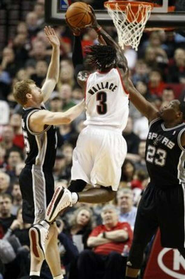 Portland Trail Blazers' Gerald Wallace (3) drives to the basket as San Antonio Spurs' Matt Bonner, left, and teammate Eric Dawson (23) defends in the first quarter of an NBA basketball game, Tuesday, Feb. 21, 2012, in Portland, Ore. (AP Photo/Rick Bowmer) (AP)