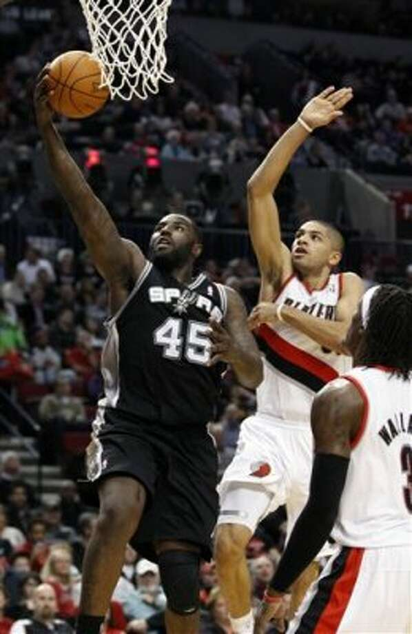 San Antonio Spurs' DeJuan Blair (45) lays the ball up as Portland Trail Blazers' Nicolas Batum, right, defends in the second quarter of an NBA basketball game, Tuesday, Feb. 21, 2012, in Portland, Ore. (AP Photo/Rick Bowmer) (AP)