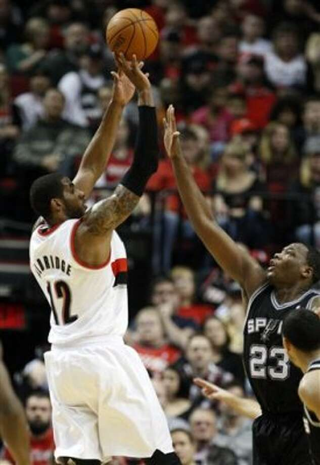 Portland Trail Blazers' LaMarcus Aldridge (12) shoots as San Antonio Spurs' Eric Dawson (23) defends in the second quarter of an NBA basketball game, Tuesday, Feb. 21, 2012, in Portland, Ore. (AP Photo/Rick Bowmer) (AP)
