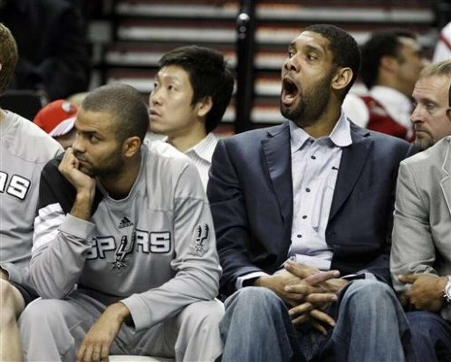 San Antonio Spurs' Tony Parker, left, looks on as teammate Tim Duncan, right, yawns in the fourth quarter during an NBA basketball game with the Portland Trail Blazers Tuesday, Feb. 21, 2012, in Portland, Ore. The Trail Blazers defeated the Spurs 137-97. Both Parker and Duncan sat the game out on the bench. (AP Photo/Rick Bowmer) (AP)