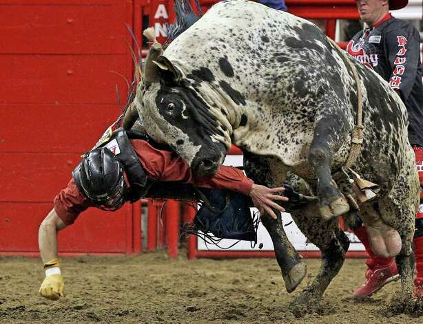 Despite this awkward dismount, Ardie Maier came out of the first round as the leader with a score of 77 in the bull riding event at the San Antonio Stock Show & Rodeo on Tuesday, Feb. 21, 2012. Photo: TOM REEL, San Antonio Express-News / San Antonio Express-News