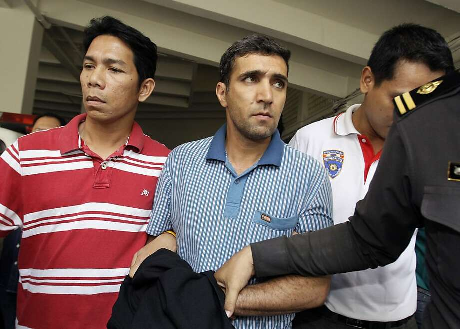 In this Thursday, Feb. 16, 2012 file photo, Thai immigration officers escort detained Iranian Mohammad Kharzei, center, at the immigration headquarters in Bangkok, Thailand. In Bangkok, the three Iranian suspects in custody appeared to take advantage of Thailand's foreigner-friendly culture to live openly while allegedly putting together a bomb cache whose targets, police say, included the Israeli Embassy. Photo: Sakchai Lalit, Associated Press