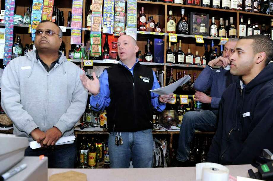 Rocky Patel, left, and Mitch Ancono, center, speak to a crowd gathered Wednesday morning at Danbury Liquor on White Street to talk about the state's proposal to allow liquor sales on Sunday. Photo taken Wednesday, Feb. 22, 2012. Photo: Carol Kaliff / The News-Times