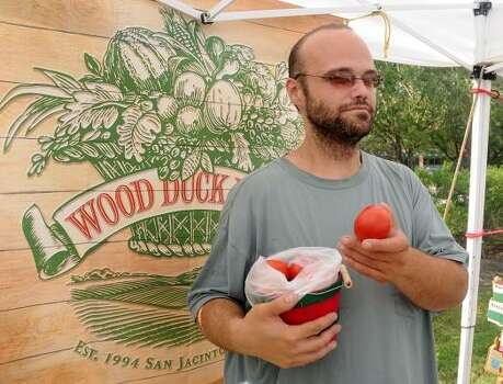 Work Duck Farm salesman Jose Estrade shows off the tomatoes for sale at the farm's booth during the Grogan's Mill Village Farmer's Market at Grogan's Mill Village Shopping Center.