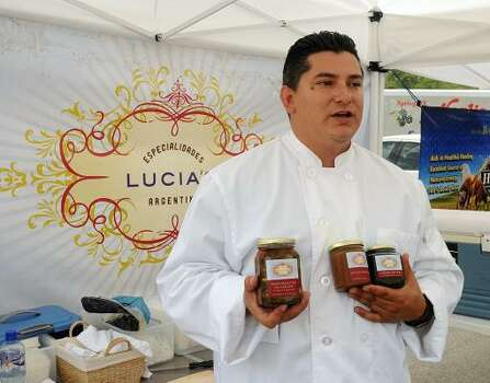 Diego Salguero shows some of his Argentina/American sauces at his booth during the Grogan's Mill Village Farmer's Market at Grogan's Mill Village Shopping Center.