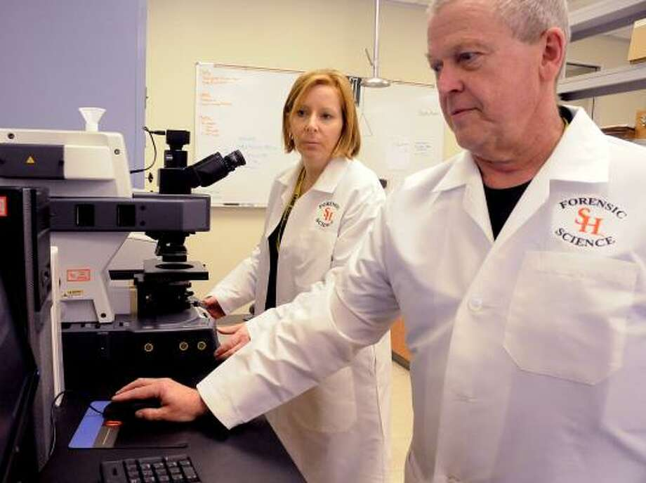 DAVID HOPPER: FOR THE CHRONICLE IN THE LAB: Dr. Sarah Kerrigan, director of the Sam Houston State University Regional Crime Lab, and lab manager Michael Manes examine evidence at the new lab at 8301 New Trails Drive, suite 125, in The Woodlands. The new c