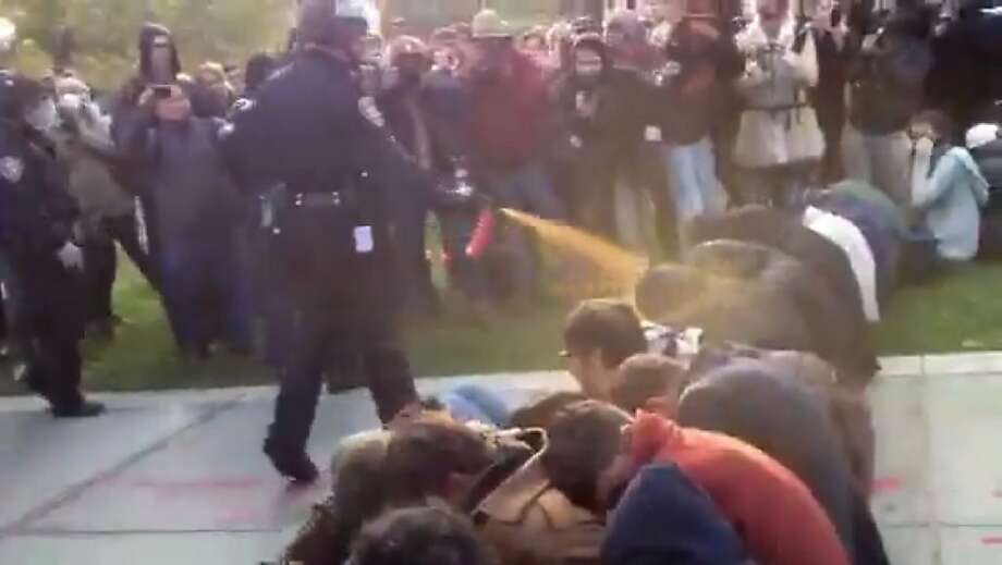 In this image made from video, a police officer uses pepper spray as he walks down a line of Occupy demonstrators sitting on the ground at the University of California, Davis on Friday, Nov. 18, 2011. The video - posted on YouTube - was shot Friday as police moved in on more than a dozen tents erected on campus and arrested 10 people, nine of them students. (AP Photo/Thomas K. Fowler) Photo: Thomas K. Fowler, Associated Press