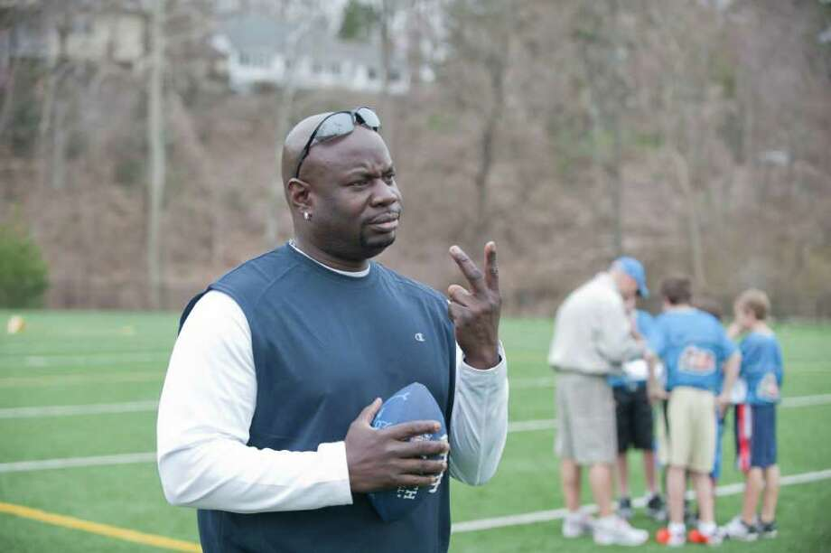 "Greenwich Police Officer Donnell ""Dee"" Fludd coaches players in the Greenwich Flag Football League April 10, 2011, at Greenwich High School. Fludd has been placed on leave amid charges of stalking and harassment. Photo: Douglas Healey, Greenwich Time File / Greenwich Time"