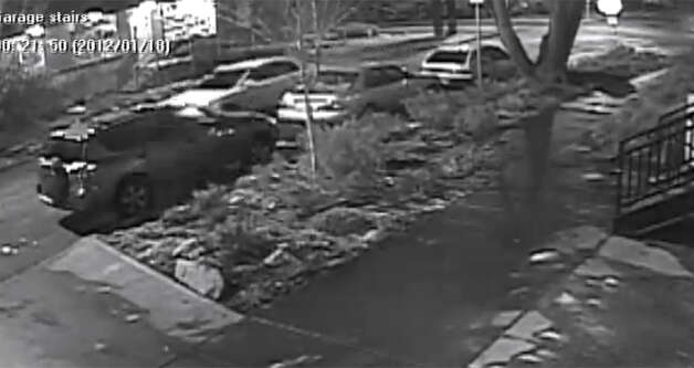 A video shows a white sedan, pictured above headed toward the left side of the screen, passing by Harvard Avenue. Police are searching for information on that vehicle, which appears to have a darker stripe painted on its side and spoiler attached to its trunk. Photo: Courtesy Of Seattle Police
