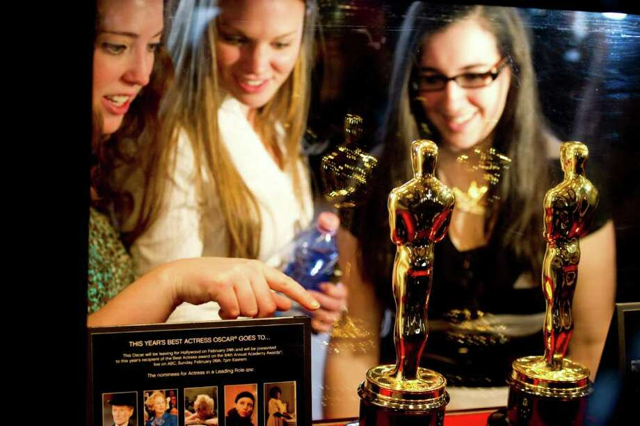 Fans view the Oscar statuettes that will be presented to the Best Actor and Best Actress winners at the 84th Academy Awards, at the opening of the Meet the Oscars exhibit at Grand Central Terminal in New York, Wednesday, Feb. 22, 2012. The Academy Awards will be held on Sunday.  (AP Photo/Charles Sykes) Photo: Charles Sykes, Associated Press / FR170266 AP